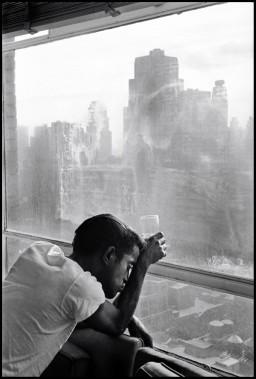 Burt Glinn, Sammy Davis Jr. looking out a Manhattan window at dawn New York, 1959.